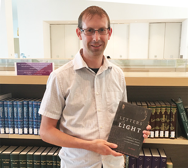 Professor JR Osborn holding his book Letters of Light at the Museum of Islamic Art in Doha